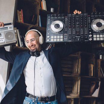 DJ, Disk Jockey, mit Radiorekorder und Controller in den Händen