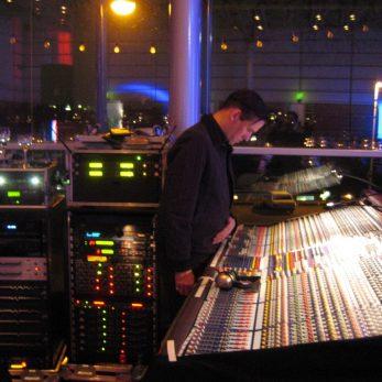Tontechniker beugt sich über sein riesengroßes Mischpult